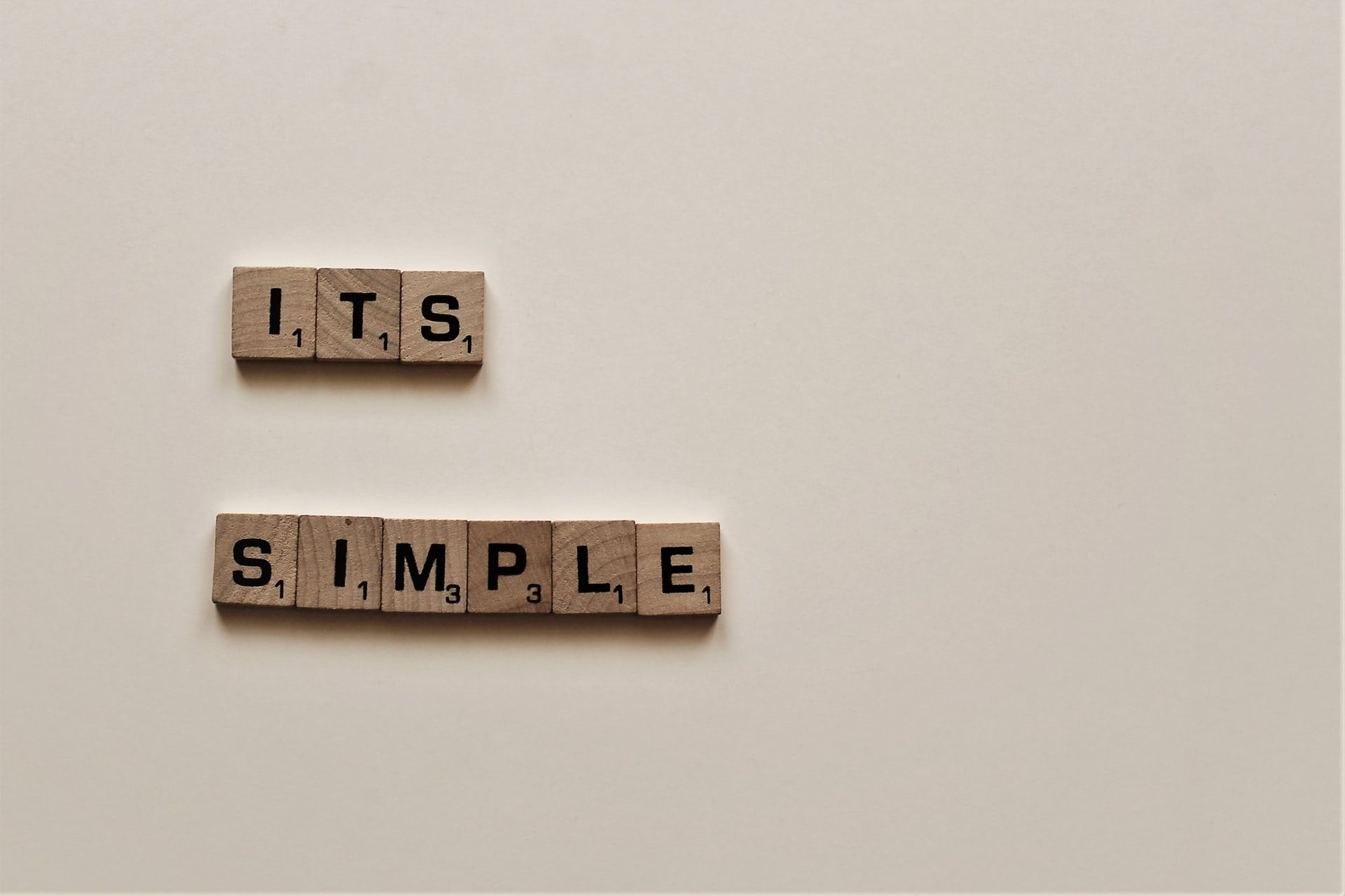 """Wooden cubes spelling out """"It's simple"""""""